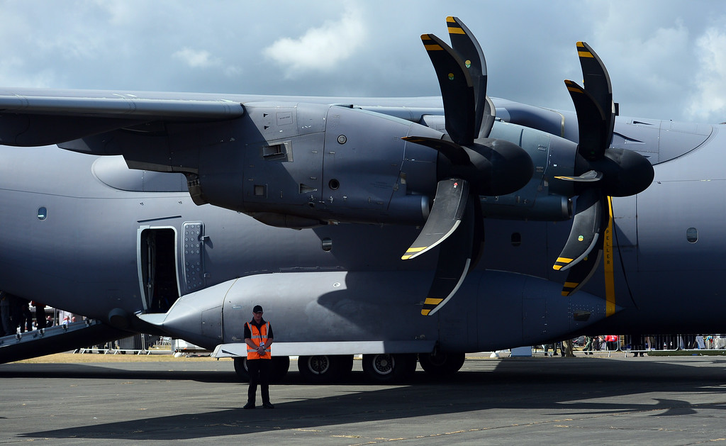 . A security guard stands beneath an Airbus A400M military transport plane on the second day of the Farnborough International Air show in Hampshire, England, on July 15, 2014. AFP PHOTO / CARL COURT/AFP/Getty Images