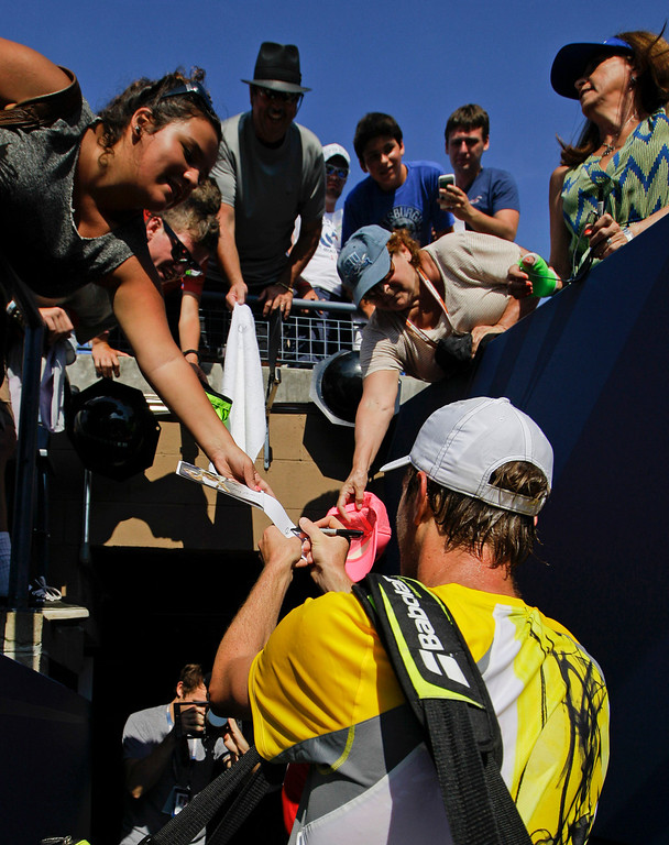 . Sam Querrey signs autographs for fans during the first round of the 2013 U.S. Open tennis tournament, Tuesday, Aug. 27, 2013, in New York. (AP Photo/Kathy Willens)