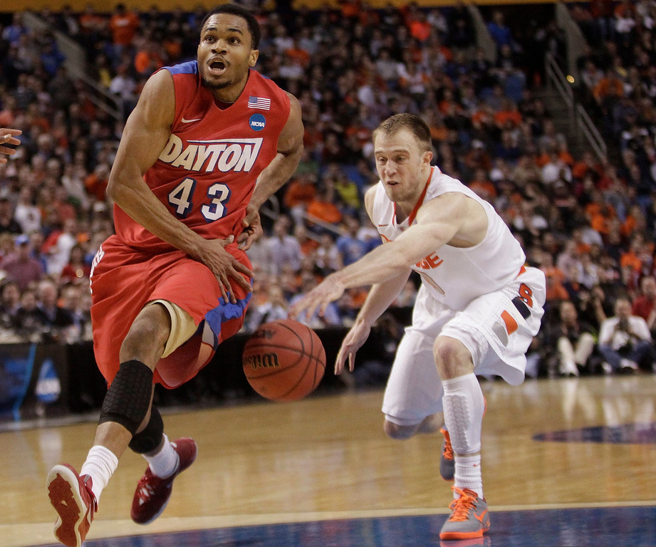 . Syracuse\'s Trevor Cooney (10) knocks the ball away from Dayton\'s Vee Sanford (43) during the first half of a third-round game in the NCAA men\'s college basketball tournament in Buffalo, N.Y., Saturday, March 22, 2014. (AP Photo/Bill Wippert)
