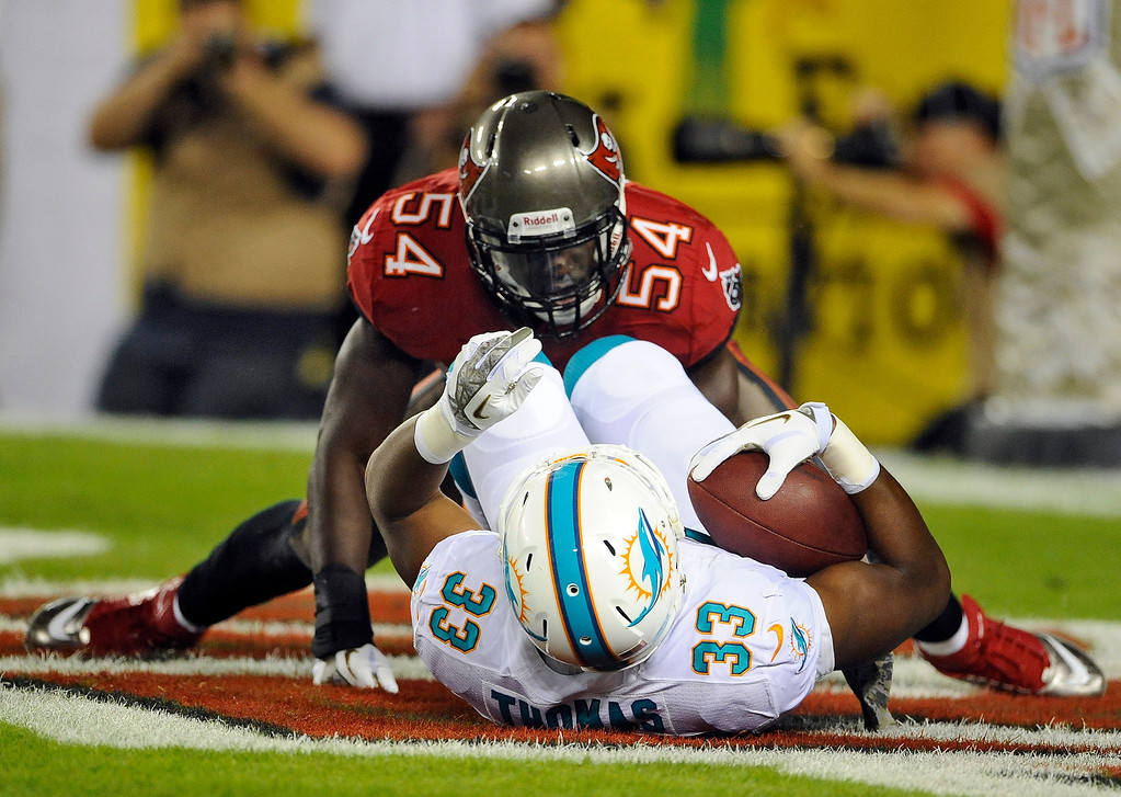 . Tampa Bay Buccaneers outside linebacker Lavonte David (54) tackles Miami Dolphins running back Daniel Thomas (33) in the end zone for a safety during the second quarter of an NFL football game Monday, Nov. 11, 2013, in Tampa, Fla. (AP Photo/Brian Blanco)