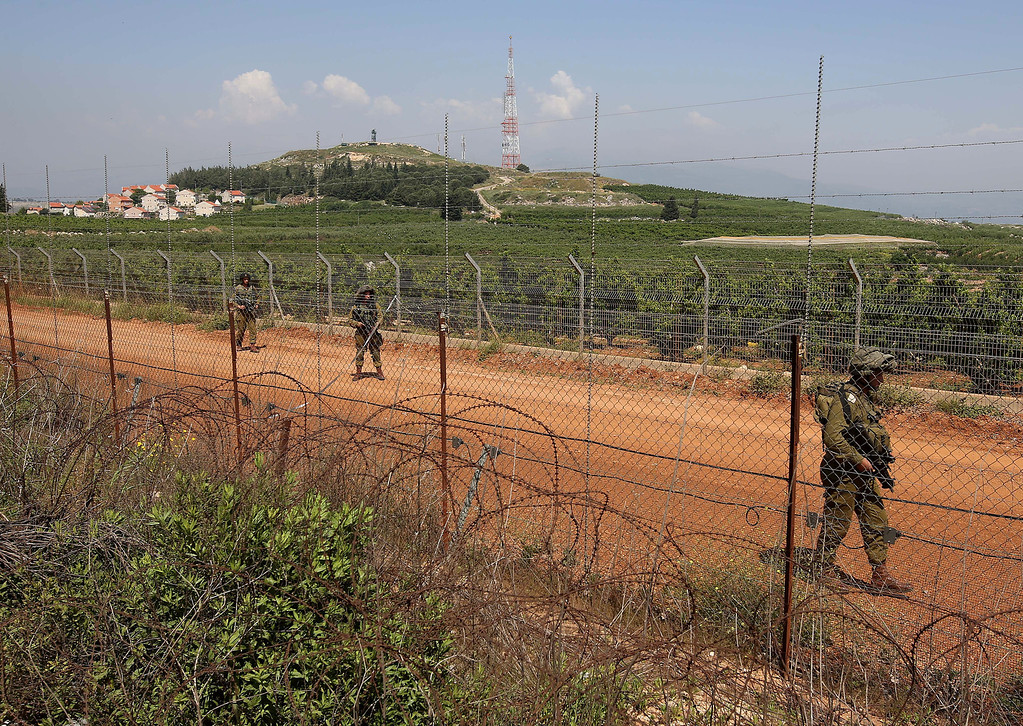 . Israeli soldiers patrol near the Israeli settlement of Metulla, background, at the Lebanese-Israeli border, near the village of Kfar Kila, Lebanon, Tuesday May 7, 2013. Syrian President Bashar Assad\'s regime has given a Palestinian militant group the go-ahead to set up missiles to attack Israel in the wake of recent Israeli airstrikes on the Syrian capital, a spokesman for the group said Tuesday. Israel\'s government has not formally confirmed involvement in the strikes on Syria. However, Israeli officials have said the attacks were meant to prevent advanced Iranian weapons from reaching Lebanon\'s Hezbollah militia, an ally of Syria and foe of Israel. (AP Photo/Hussein Malla)