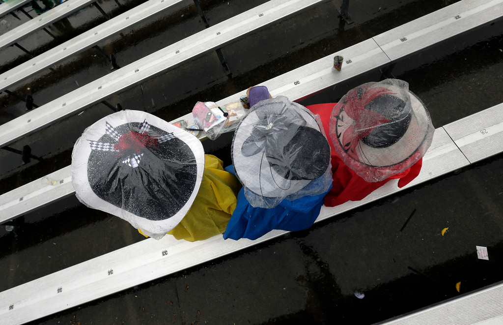 . Women protect their fancy hats with plastic as they wait for the next race before the 139th Kentucky Derby at Churchill Downs Saturday, May 4, 2013, in Louisville, Ky. (AP Photo/Charlie Riedel)