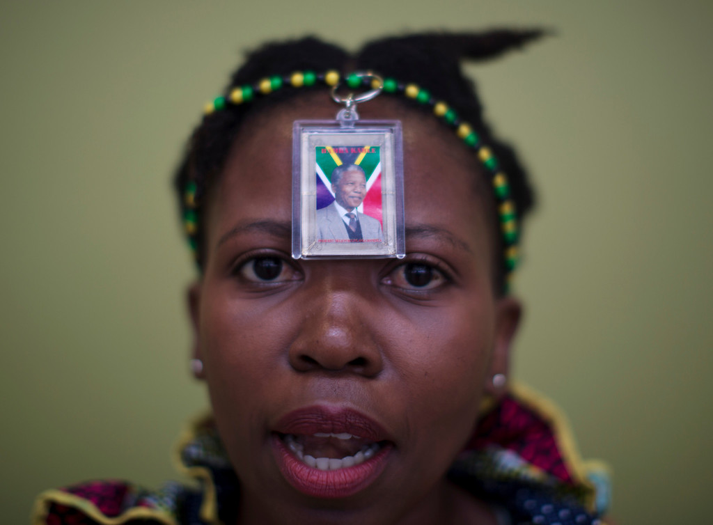 . A woman wears a photo of former South African president Nelson Mandela for his the memorial service for  at the FNB Stadium in Soweto near Johannesburg, Tuesday, Dec. 10, 2013. (AP Photo/Muhammed Muheisen)