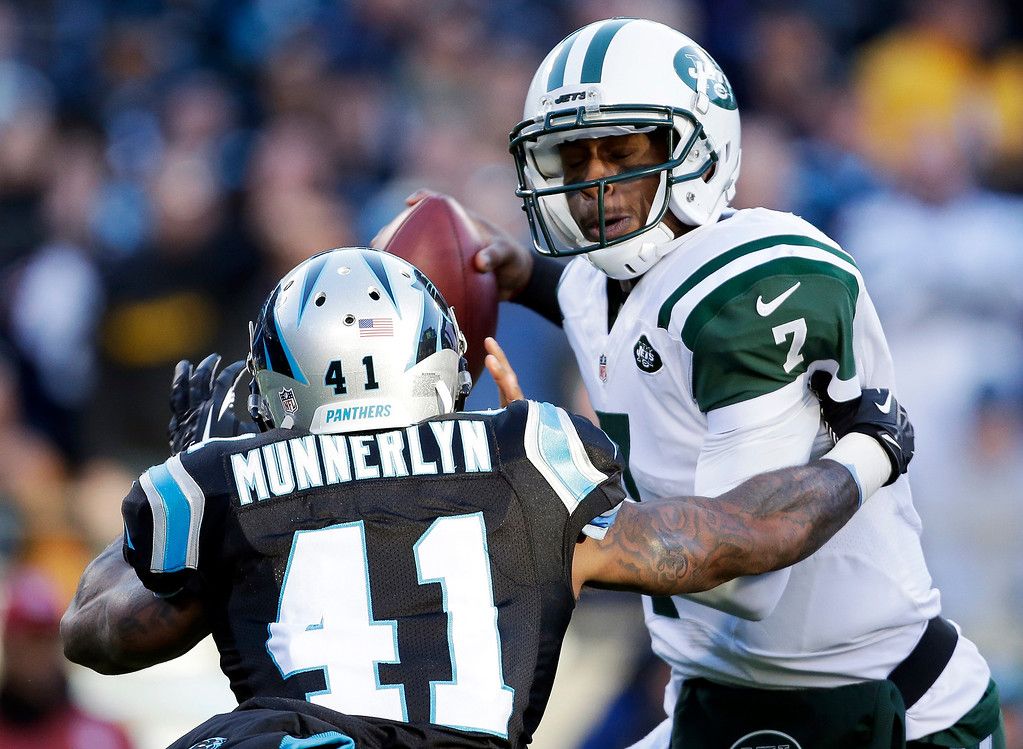 . New York Jets\' Geno Smith (7) is hit by Carolina Panthers\' Captain Munnerlyn (41) during the first half of an NFL football game in Charlotte, N.C., Sunday, Dec. 15, 2013. (AP Photo/Bob Leverone)