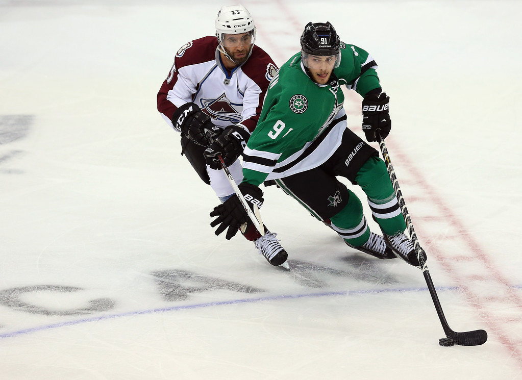 . Tyler Seguin #91 of the Dallas Stars skates the puck against Maxime Talbot #25 of the Colorado Avalanche in the third quarter at American Airlines Center on December 17, 2013 in Dallas, Texas.  (Photo by Ronald Martinez/Getty Images)