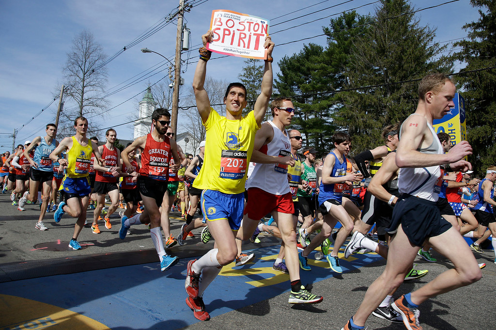 . Runners in the first wave of 9,000 cross the start line of the 118th Boston Marathon Monday, April 21, 2014 in Hopkinton, Mass.  (AP Photo/Stephan Savoia)