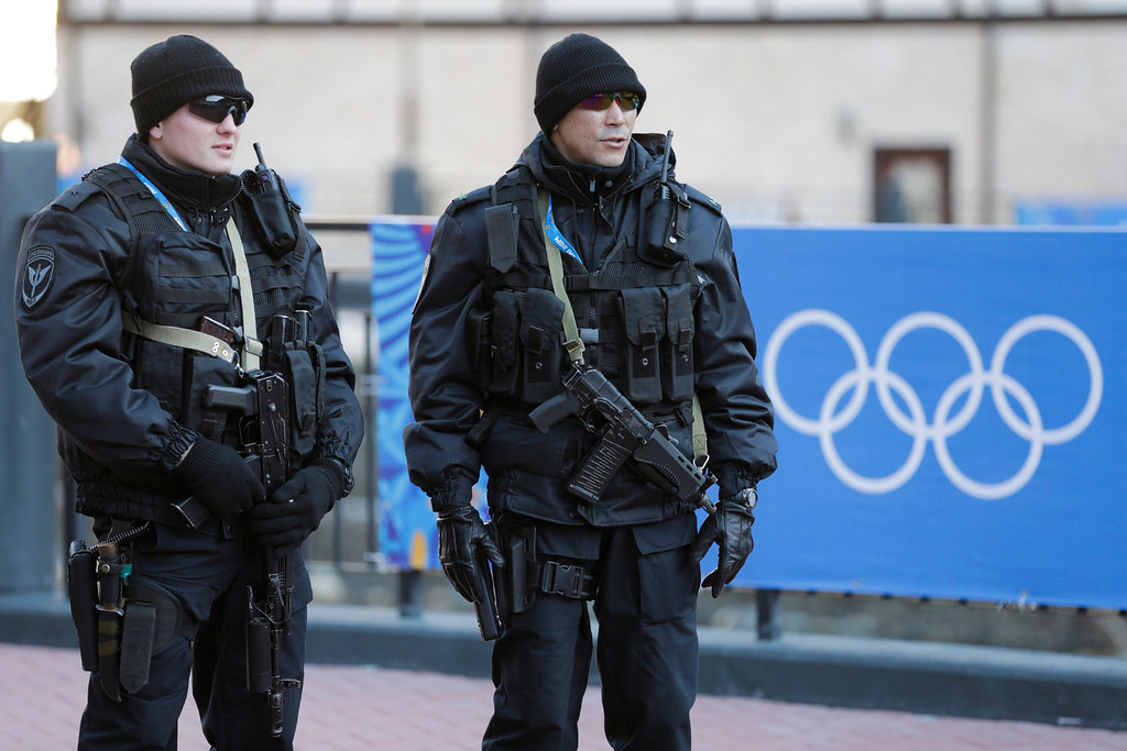 . Russian security forces stand guard as the Olympic torch makes it\'s way through the streets of the Rosa Khutor ski resort in Krasnaya Polyana, Russia at the Sochi 2014 Winter Olympics, Wednesday, Feb. 5, 2014. (AP Photo/Gero Breloer)
