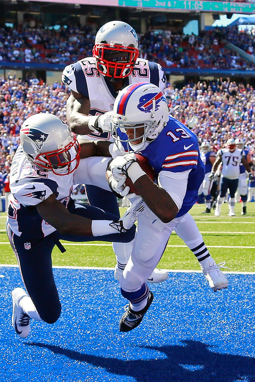 . Buffalo Bills wide receiver Steve Johnson (13) catches a touchdown pass from EJ Manuel in front of New England Patriots\' Devin McCourty (32) and Kyle Arrington (25) during the second half of an NFL football game on Sunday, Sept. 8, 2013, in Orchard Park. (AP Photo/Bill Wippert)