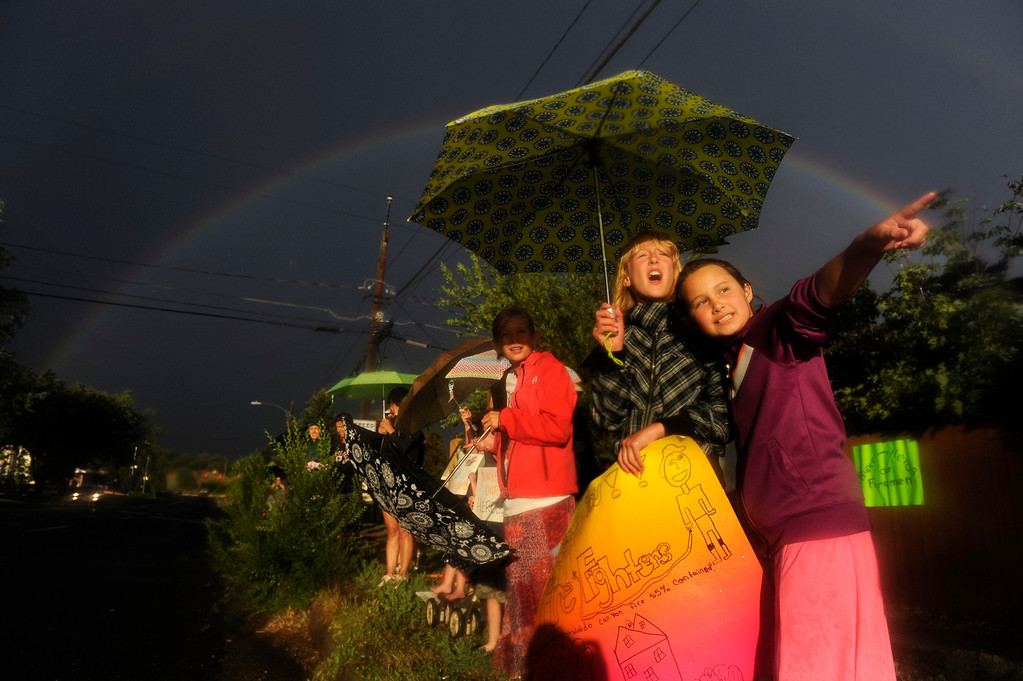 ". Lindy Walton, 10, left, Sydney Barnes, 10, and Aria Schleiker, 10, right, anticipate approaching firefighters changing shifts in Colorado Springs on Tuesday, July, 3, 2012 in the evening just after it had rained. Local residents have been gathering daily to show their support of firefighters combatting the Waldo Canyon Fire between shift changes daily at 7 a.m. and 7 p.m.. When asked why she was out supporting firefighters, Schleiker said, ""It\'s 100 degrees and above and they are probably sweating to death and I am happy they saved my school from burning down.\"" Heather Rousseau, The Denver Post"