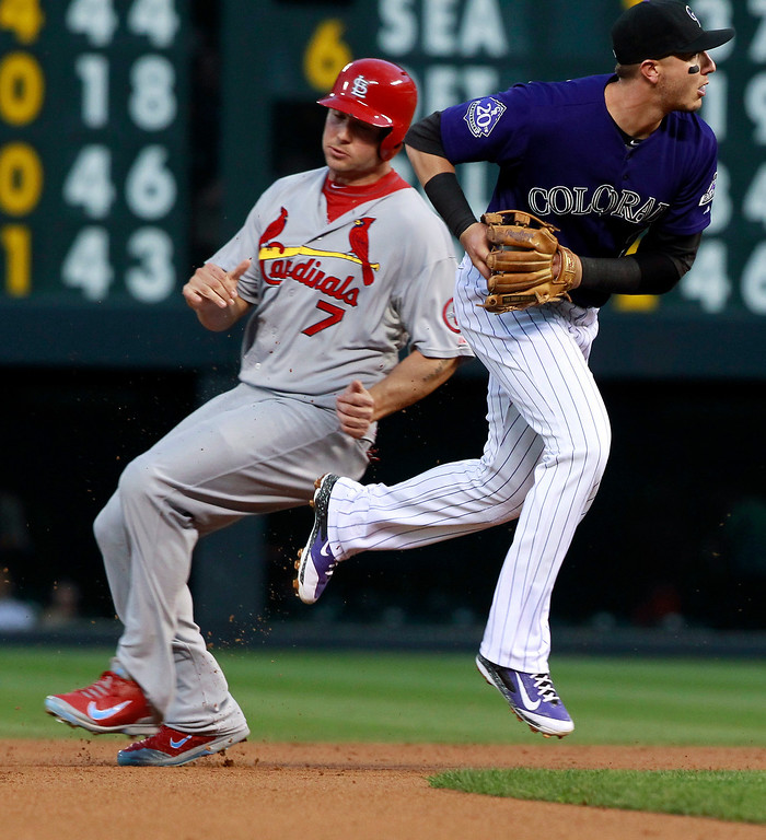 . Colorado Rockies shortstop Troy Tulowitzki, right, jumps out of the way after forcing out St. Louis Cardinals\' Matt Holliday at second base on a ground ball hit by Carlos Beltran in the first inning of a baseball game in Denver on Tuesday, Sept. 17, 2013. (AP Photo/David Zalubowski)