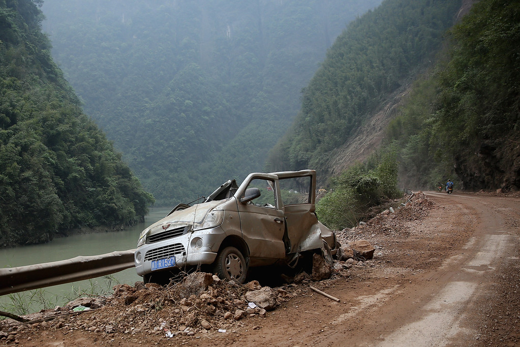 . A car destroyed by boulders is seen on the way to BaoXing county, one of the hardest hit areas of the earthquake zone, on April 22, 2013 in Baoxing county of Ya An, China.   (Photo by Feng Li/Getty Images)