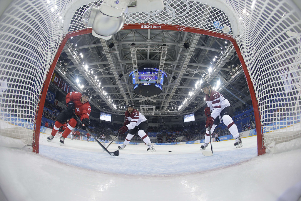 . Switzerland\'s Reto Suri (L) vies for the puck with Latvia\'s Vitalijs Pavlovs during the Men\'s Ice Hockey Group C match between Latvia and Switzerland at the Sochi Winter Olympics on February 12, 2014 at the Shayba Arena.    MATT SLOCUM/AFP/Getty Images