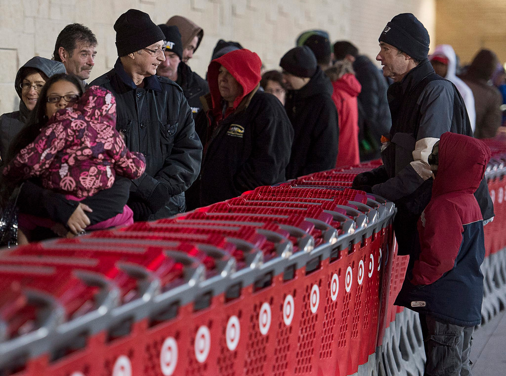 . Shoppers wait in line at a Target store in Dartmouth, Nova Scotia, on Friday, Nov. 29, 2013. Black Friday, thought to be the most important shopping day of the year in the United States, is having an impact on Canadian sales as retailers work to keep consumers home, north of the border. (AP Photo/The Canadian Press, Andrew Vaughan)