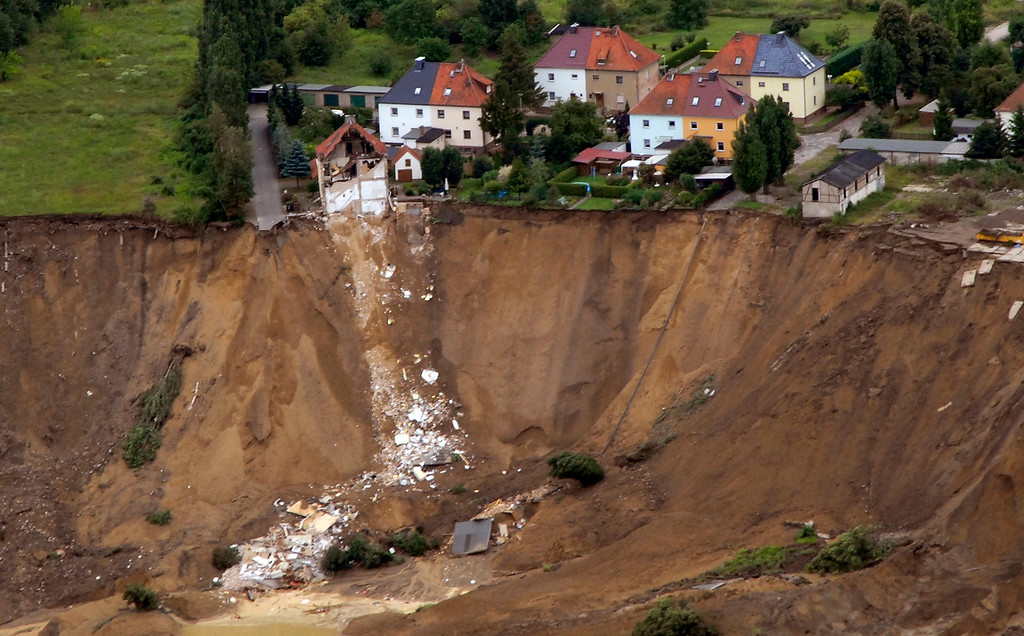 . An aerial view shows the debris of a residential building and a destroyed road in the village of Nachterstedt, July 18, 2009. Three residents were missing in the eastern German village of Nachterstedt after their lakeside home and another building suddenly collapsed into the water. A 350-meter stretch of shoreline gave way next to an old open-cast coal mine converted to a lake, about 170 kilometers south-west of Berlin.      REUTERS/Handout/Gemeindeverwaltung Nachterstedt