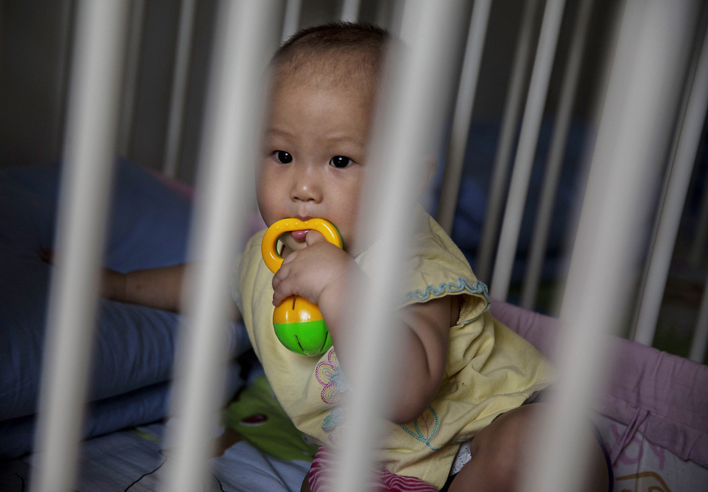 . A young orphaned Chinese girl sits in a crib at a foster care center on April 2, 2014 in Beijing, China.  (Photo by Kevin Frayer/Getty Images)