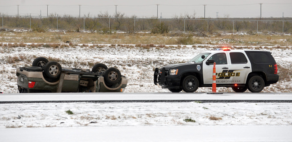 . Odessa, Texas Police respond to a rolled over vehicle that crashed on the slick eastbound lanes of Interstate 20, Friday morning, Dec. 6, 2013, in Odessa, Texas. Winter storm and ice warnings are in effect through much of today for parts of six states in the Midwest, including Texas, Missouri, Illinois and Indiana. (AP Photo/Odessa American, Mark Sterkel)