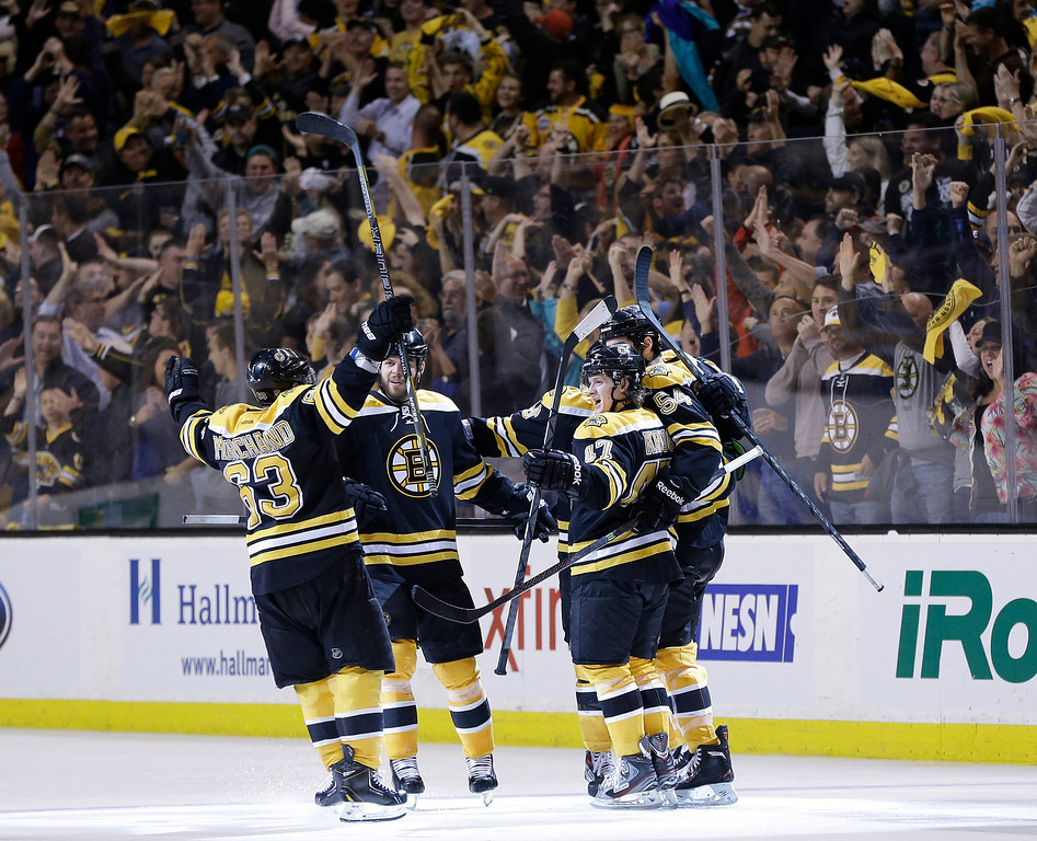 . Boston Bruins left wing Brad Marchand (63), right wing Nathan Horton, second from left, and defenseman Torey Krug (47) celebrate a goal by defenseman Adam McQuaid (54) during the third period of Game 4 in the Eastern Conference finals of the NHL hockey Stanley Cup playoffs against the Pittsburgh Penguins, in Boston on Friday, June 7, 2013. (AP Photo/Elise Amendola)