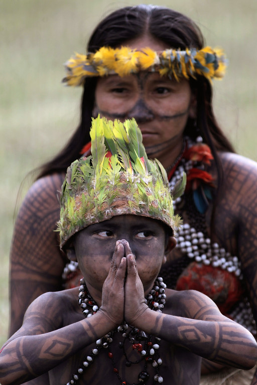 . A young Indian from the Munduruku tribe and his mother protest the construction of the Belo Monte dam outside Congress in Brasilia, Brazil, Thursday, June 6, 2013. The Indians, who had been occupying the controversial Belo Monte dam which is being built in the Amazon on the Xingu River, were flown to Brasilia by the government for talks to try to end the occupation. Environmentalists and indigenous groups say the dam would devastate wildlife and the livelihoods of thousands of people who live in the area to be flooded. (AP Photo/Eraldo Peres)