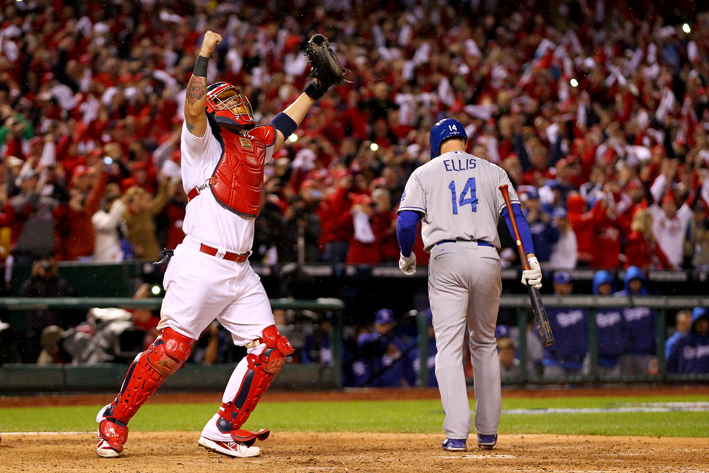 . ST LOUIS, MO - OCTOBER 18:  Yadier Molina #4 of the St. Louis Cardinals celebrates as Mark Ellis #14 of the Los Angeles Dodgers strikes out as the Cardinals defeat the Los Angeles Dodgers 9-0 in Game Six of the National League Championship Series at Busch Stadium on October 18, 2013 in St Louis, Missouri.  (Photo by Dilip Vishwanat/Getty Images)