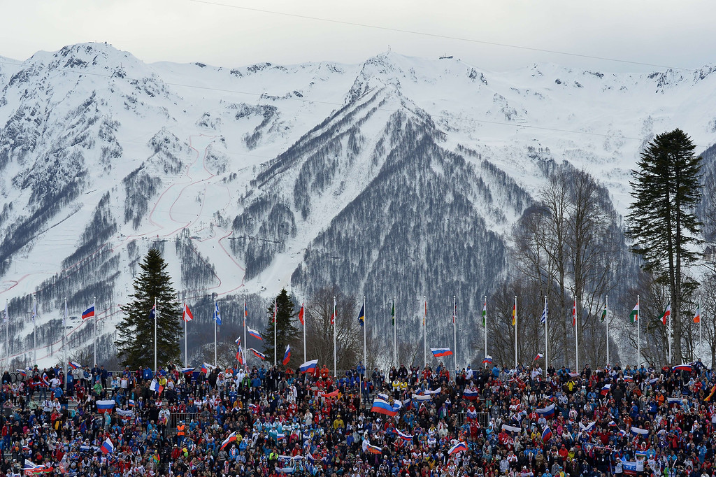 . Fans wave flags from the stands as they watch the Men\'s Cross-Country Skiing 15km Classic at the Laura Cross-Country Ski and Biathlon Center during the Sochi Winter Olympics on February 14, 2014 in Rosa Khutor near Sochi. In the background is the Alpine Center ski course marked out in red.  ALBERTO PIZZOLI/AFP/Getty Images