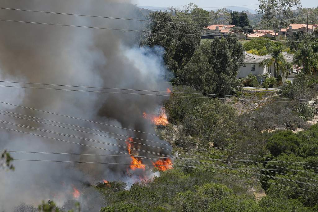 . Wildfire climbs a canyon toward homes Wednesday, May 14, 2014, in Carlsbad, Calif. More wildfires broke out Wednesday in San Diego County, threatening homes in Carlsbad and forcing the evacuations of military housing and an elementary school at Camp Pendleton , as Southern California is in the grip of a heat wave. (AP Photo)