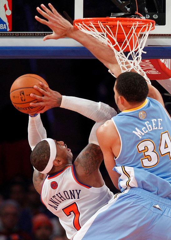 . New York Knicks\' Carmelo Anthony (7) shoots against Denver Nuggets\' JaVale McGee (34) during an NBA basketball game, Sunday, Dec. 9, 2012, in New York.  New York beat Denver, 112-106. (AP Photo/Jason DeCrow)