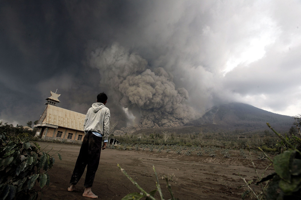 . A resident looks  at giant volcanic ash clouds from a village in Karo district during the eruption of Mount Sinabung volcano located in Indonesia\'s Sumatra island on February 1, 2014. AFP PHOTO / CHAIDEER  MAHYUDDIN/AFP/Getty Images