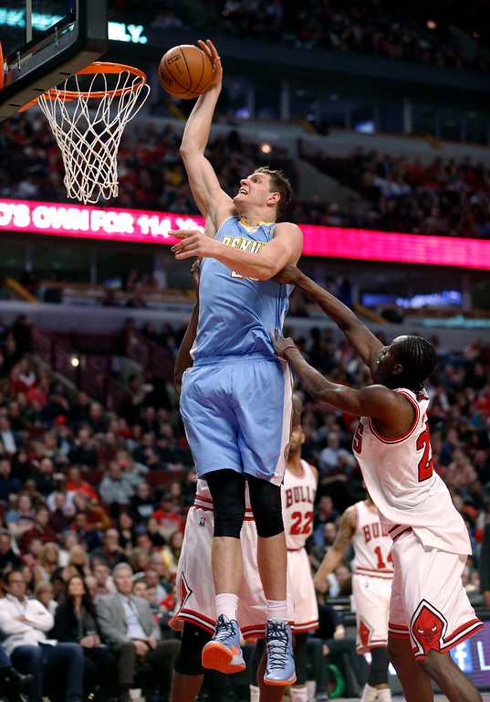 . Denver Nuggets center Timofey Mozgov (25) dunks over Chicago Bulls guard Tony Snell during the first half of an NBA basketball game Friday, Feb. 21, 2014, in Chicago. (AP Photo/Charles Rex Arbogast)