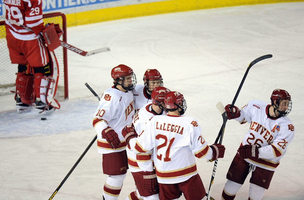 . University of Denver\'s Shawn Ostrow (26), right, celebrates scoring a goal from Boston University goalie Matt O\'Connor (29), left, with his teammates in the 1st period of the game at Magness Arena on in Denver on Saturday, Dec. 29, 2012. Hyoung Chang, The Denver Post
