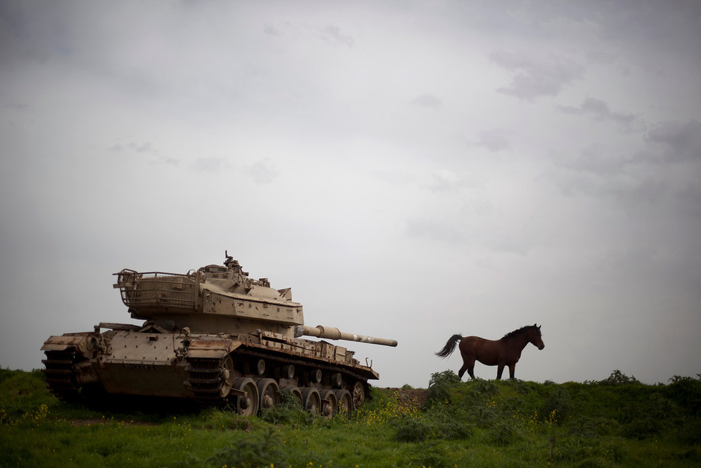 . A horse runs in a pasture next to an old Israeli tank in the Israeli-controlled Golan Heights on the border with Syria, Friday, March 8, 2013. Israel captured the Golan from Syria in 1967 Mideast war. (AP Photo/Ariel Schalit)