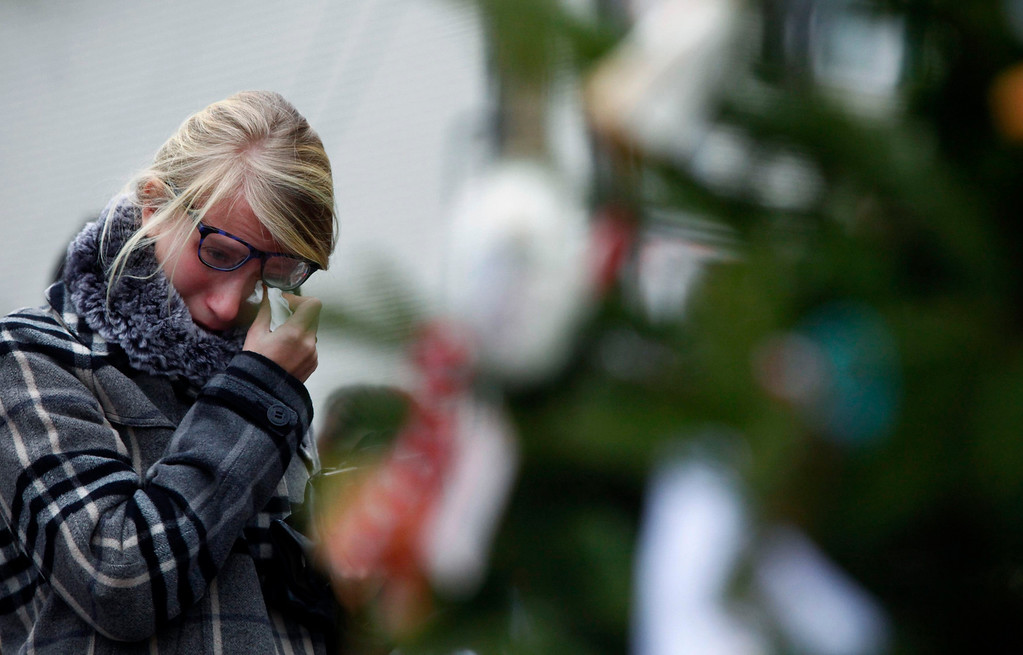 . A woman wipes her eye as she visits a makeshift memorial near Sandy Hook Elementary School in Newtown, Connecticut, December 16, 2012. Twelve girls, eight boys and six adult women were killed in the shooting on Friday at the Sandy Hook Elementary School in Newtown. REUTERS/Eric Thayer