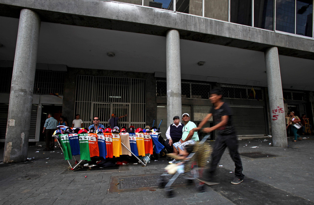". A street vendor\'s table is full of Chavez baseball caps and T-shirts with a words in Spanish ""I am Chavez\"" in Caracas, Venezuela, Monday, March 11, 2013. At Caracas\' choked Bolivar Plaza, a favorite hangout for the late president\'s supporters, shoppers can find virtually anything Chavez-related the mind can dream up. (AP Photo/Fernando Llano)"