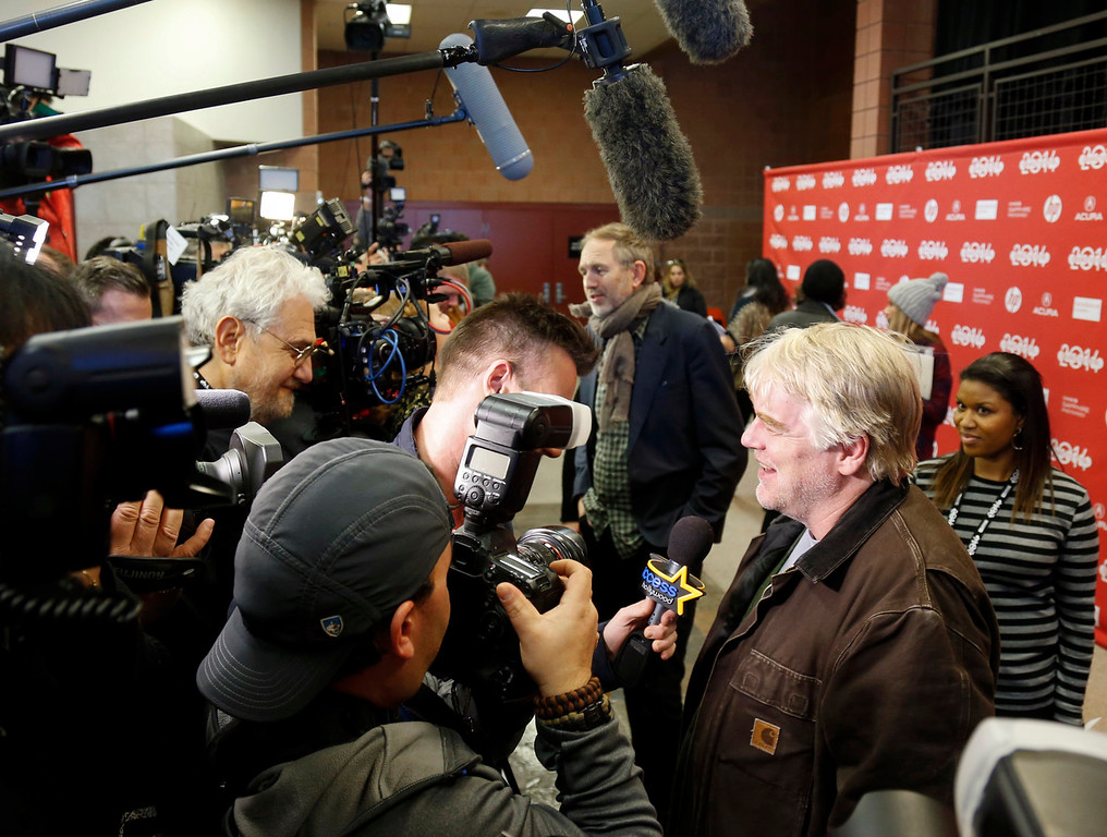 ". Cast member Philip Seymour Hoffman, right, and Director Anton Corbijn, rear, are interviewed at the premiere of the film ""A Most Wanted Man\"" during the 2014 Sundance Film Festival, on Sunday, Jan. 19, 2014, in Park City, Utah. (Photo by Danny Moloshok/Invision/AP)"