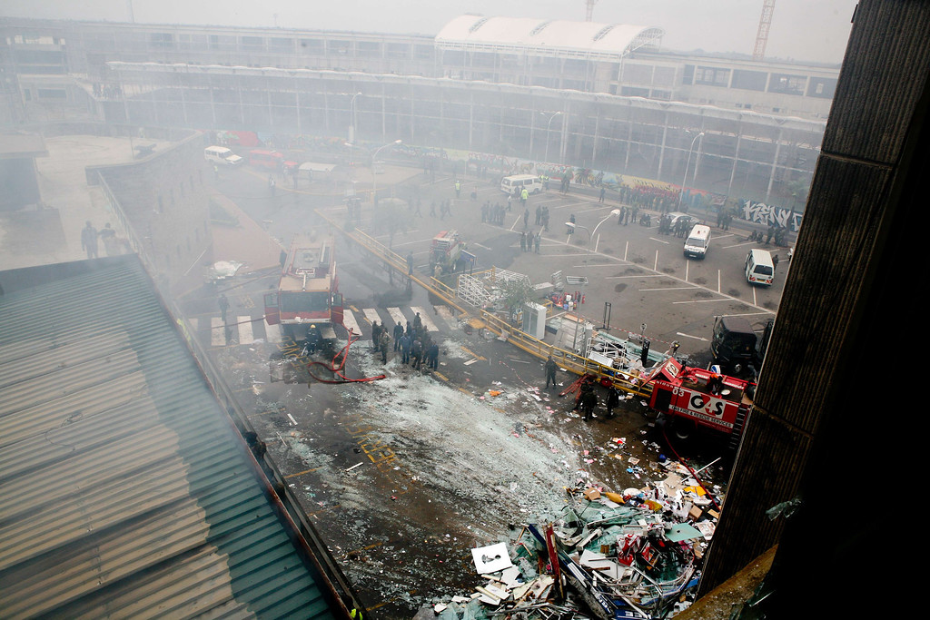 . Fire crews and debris are pictured outside Jomo Kenyatta international airport in Nairobi on August 7, 2013. AFP PHOTO/Lama KABBANI/AFP/Getty Images