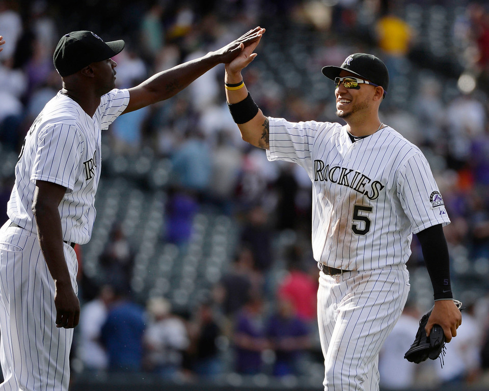 . Colorado Rockies outfielder, Carlos Gonzalez, right, celebrates with relief pitcher, LaTroy Hawkins after defeating the Chicago WhiteSox 10-4 at Coors Field  Wednesday afternoon, April 09, 2014. (Photo By Andy Cross / The Denver Post)