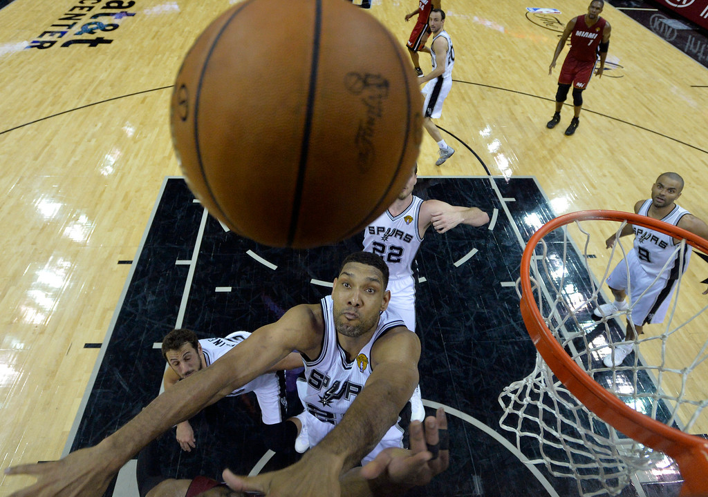 . San Antonio Spurs forward Tim Duncan (21) goes after the ball against the Miami Heat during the first half in Game 1 of the NBA basketball finals on Thursday, June 5, 2014 in San Antonio. (AP Photo/Soobum Im, Pool)