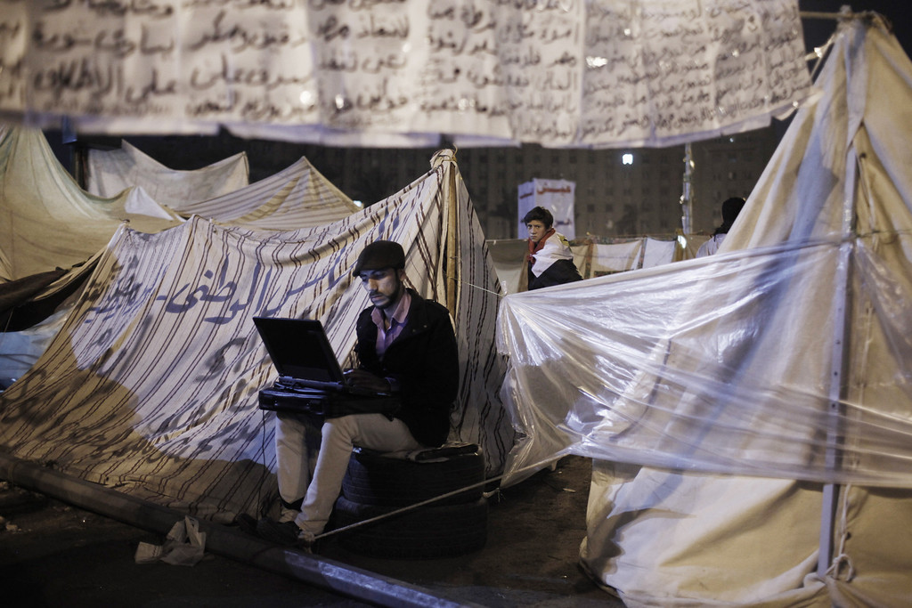 . CAIRO, EGYPT - JANUARY 25: An Egyptian protester works on a laptop computer while sitting amongst tents pitched in Tahrir Square on January 25, in Cairo, Egypt. Thousands of protesters converged on the capital\'s iconic Tahrir Square on January 25, to mark the second anniversary of the overthrow of former President Hosni Mubarak\'s regime. (Photo by Ed Giles/Getty Images).