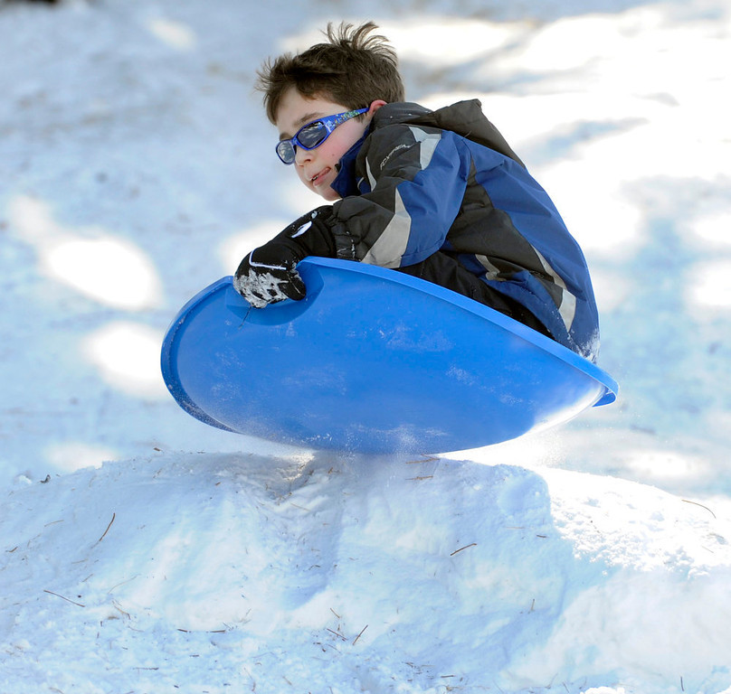 . David Budreau, 8, vaults himself off a small jump as he and several families gather at Robinson Park to get in some sledding before the weekend snow begins to melt later in the week with warmer weather forecasted. These Denver families and their kids begin their spring break week today. (Photo By Kathryn Scott Osler/The Denver Post)