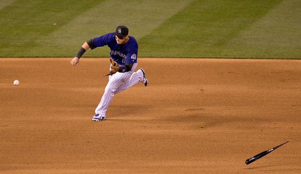. Shortstop Troy Tulowitzki #2 of the Colorado Rockies fields a ground ball while avoiding a broken bat from Tyler Flowers #21 of the Chicago White Sox during the fifth inning at Coors Field on April 7, 2014 in Denver, Colorado. (Photo by Justin Edmonds/Getty Images)