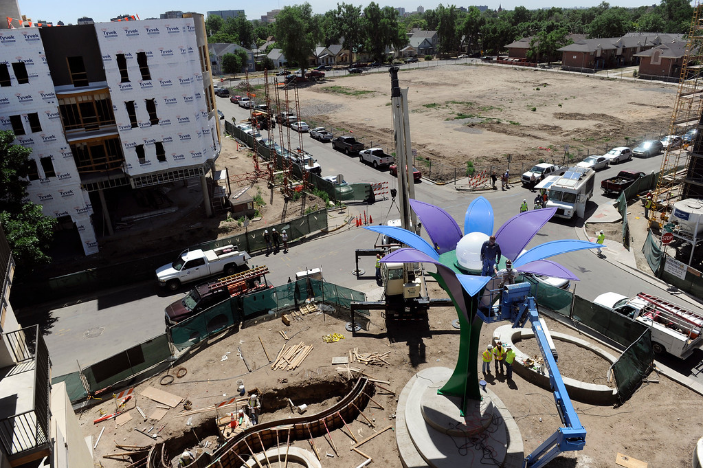 . Crews bolt down the white bulb on the 30 foot-tall, 10-ton metal sculpture of a large flower titled Flor De La Alma by Denver artist Emanuel Martinez, that serves as the center of the flower, Tuesday, June 25, 2013. (Photo By Kathryn Scott Osler/The Denver Post)
