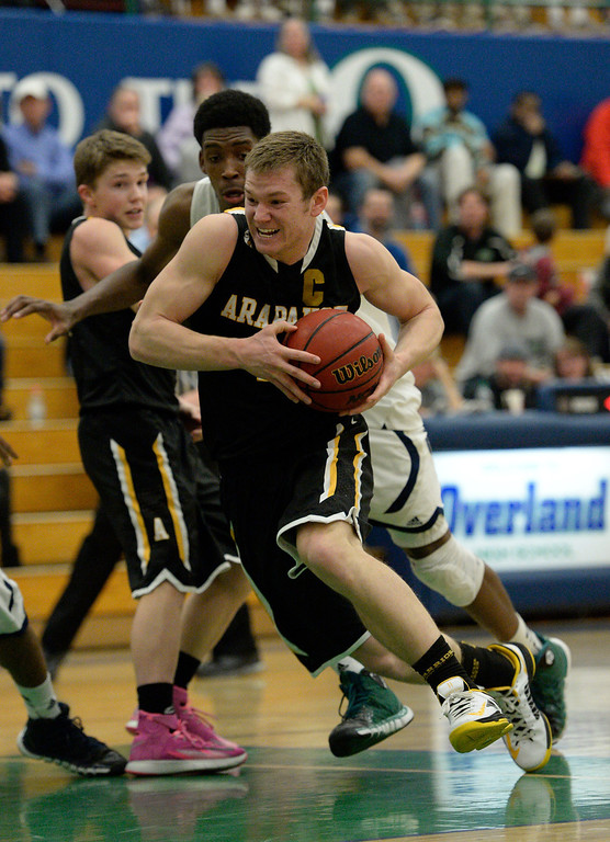 . AURORA, CO - FEBRUARY 12: Arapahoe Ethan Brunhofer (11) drives to the basket for a score pas Overland De\'Ron Davis (20) during their 5A basketball game February 12, 2014 in Aurora. Arapahoe Brunhofer was held to 6 point in the first half and scored 30 points in the second half in a losing effort. Overland defeated Arapahoe 72-65. (Photo by John Leyba/The Denver Post)