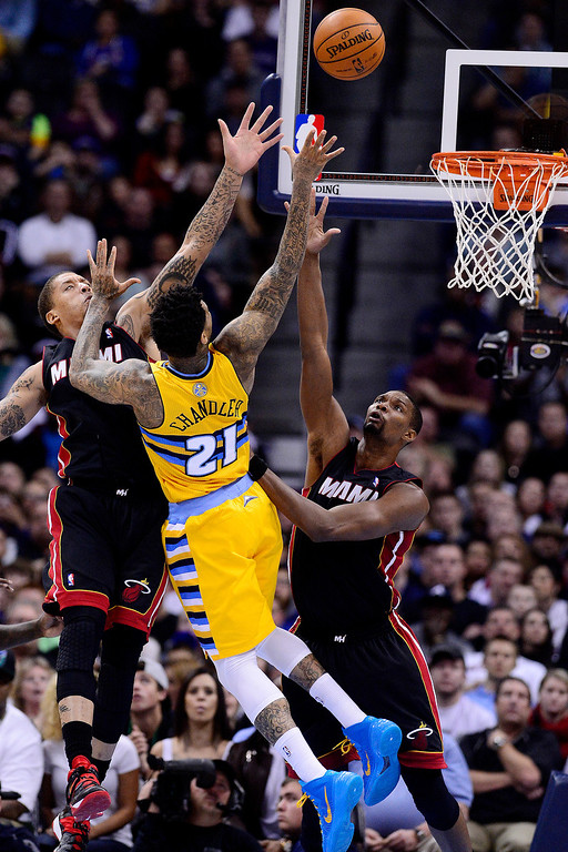 . Michael Beasley (8) of the Miami Heat and Chris Bosh (1) defend Wilson Chandler (21) of the Denver Nuggets during the second half of Miami\'s 97-94 win.  (Photo by AAron Ontiveroz/The Denver Post)