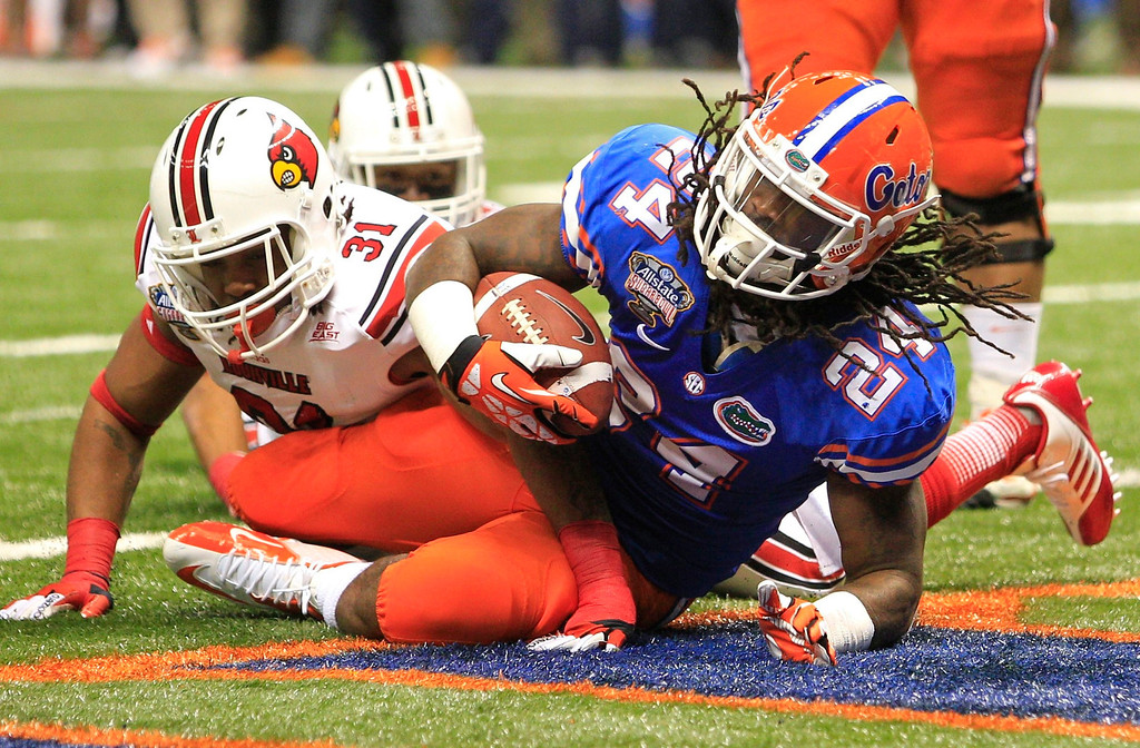 . Florida Gators running back Matt Jones (R) scores a second quarter touchdown as Louisville Cardinals linebacker Champ Lee (31) looks on, during their 2013 Allstate Sugar Bowl NCAA football game in New Orleans, Louisiana January 2, 2013.  REUTERS/Sean Gardner