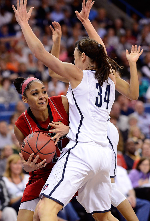 . Bria Smith #21 of the Louisville Cardinals handles the ball against Kelly Faris #34 and Kaleena Mosqueda-Lewis #23 of the Connecticut Huskies in the first half during the 2013 NCAA Women\'s Final Four Championship at New Orleans Arena on April 9, 2013 in New Orleans, Louisiana.  (Photo by Stacy Revere/Getty Images)