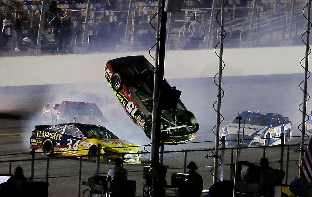 . Clint Bowyer (15) flips upside down as he is involved in a multi-car crash with David Ragan (34), Carl Edwards (99) and others on the final lap of  the second of two NASCAR Sprint Cup qualifying auto races at Daytona International Speedway in Daytona Beach, Fla., Thursday, Feb. 20, 2014. (AP Photo/John Raoux)