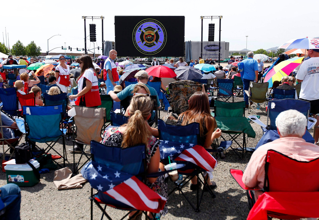 . Overflow crowds watch large TV screens as they sit outside a memorial for the fallen members of Prescott Fire Department\'s Granite Mountain Hotshots team in Prescott Valley, Arizona July 9, 2013.  REUTERS/Mike Blake