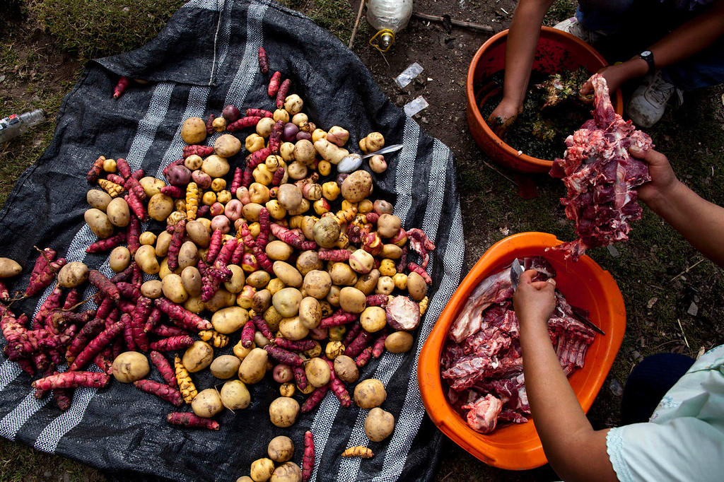 """. Women prepare \""""Pachamanca,\"""" a feast of meats, vegetables and herbs, buried in a pit along with hot stones and roasted, in honor of a mass burial and to mark Father\'s Day, in Chaca, Peru. The remains of residents that were exhumed in 2012 from a mass grave and released to family members on June 13, 2013 were interred in a mass burial at the Chaca cemetery. On Jan. 8, 1988, a group of Chaca villagers were tortured and killed by Shining Path militants in retaliation for forming a self-defense committee.   (AP Photo/Rodrigo Abd)"""