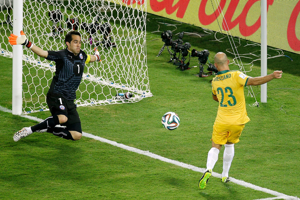 . Chile\'s goalkeeper Claudio Bravo, left, blocks a shot by Australia\'s Mark Bresciano during the group B World Cup soccer match between Chile and Australia in the Arena Pantanal in Cuiaba, Brazil, Friday, June 13, 2014. (AP Photo/Michael Sohn)