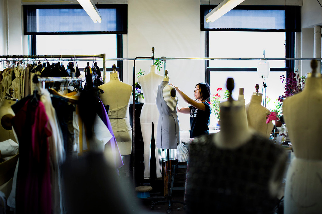 . Designer Annie Le handles a dress on a mannequin in the production room of the New York studio of fashion designer Carmen Marc Valvo. Valvo will show his Spring 2014 collection on Sept. 6 at Lincoln Center in New York. (AP Photo/John Minchillo)
