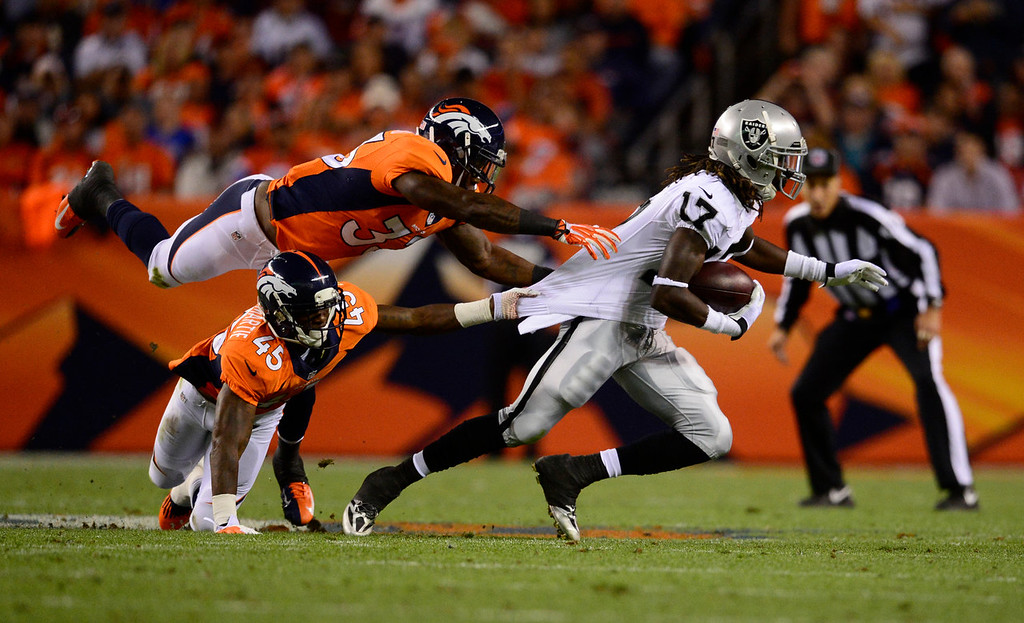 . Oakland Raiders wide receiver Denarius Moore (17) breaks a tackle by Denver Broncos cornerback Dominique Rodgers-Cromartie (45) and Denver Broncos strong safety Duke Ihenacho (33) and scores a touchdown in the second quarter. The Denver Broncos took on the Oakland Raiders at Sports Authority Field at Mile High in Denver on September 23, 2013. (Photo by AAron Ontiveroz/The Denver Post)